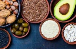 Fontes gordas saudáveis do vegetariano Porcas, abacate, azeitonas, sementes Foto de Stock