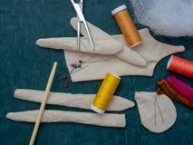 Fontes para costurar uma boneca de pano em um fundo escuro fotos de stock
