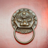 Foo Dog ou Lion Door Knocker na porta do vermelho do Pequim Fotografia de Stock