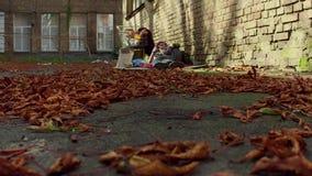 Fooage των πεσμένων φύλλων στο έδαφος και τον άστεγο ύπνο ατόμων στο έδαφος στο σκηνικό φιλμ μικρού μήκους