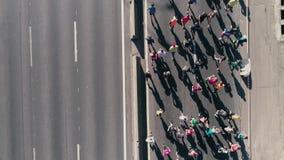 fooage aéreo do zangão 4K Maratona que corre na rua Câmera de seguimento fim da vista superior acima video estoque