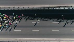 fooage aéreo do zangão 4K Maratona que corre na rua Grupo de atletas Vista superior video estoque