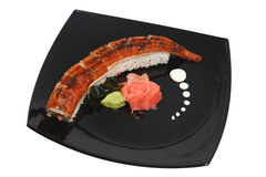 Food. Eel on a black plate and rose Stock Photography