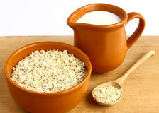 Food. A bowl of oatmeal and a jug of milk on wooden background Stock Photography