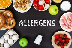 Food allergens as milk, oranges, tomatoes, garlic, shrimp, peanuts, eggs, apples, bread, strawberries on wooden table royalty free stock photo