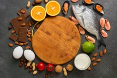 Food allergens. Round cutting board and frame and allergenic products. Top view, flat lay copy space