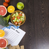 Food And Sheet Of Paper With A Diet Plan On A Dark Wooden Table. Royalty Free Stock Image