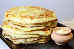 Food. Appetizing baked thick yeast pancakes are stacked on a plate on the table. stock images