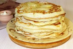 Food. Appetizing baked thick yeast pancakes are stacked on a plate on the table. stock photo