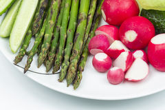 Food arrangement with fresh red radishes, cucumbers, lettuce and grilled asparagus. On a white plate Royalty Free Stock Photo