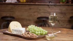 Food art concept of a glass of white wine and cheese appetizer. Walnuts and honey for great tasting experience stock video footage