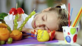 Decorative fruit food. Food art creative concepts. A little girl looks at a decorative palm tree, a man and a mouse made of fruit. On the table lie grapes stock video footage