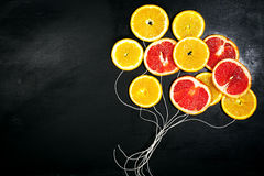Food Art. Fruit slices on a dark Chalkboard Background with strings. Balloons from fruit slices. Healthy life, detox concept. royalty free stock image