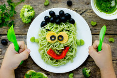 Food art idea for kids green monster from spaghetti, olives and. Bell pepper. Child eating concept top view Royalty Free Stock Images
