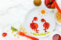 Food art idea - strawberry bird flamingo on a white plate for he. Althy summer dessert royalty free stock images