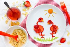 Food art idea - strawberry bird flamingo. On a white plate for healthy summer dessert royalty free stock photo