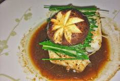 Food Artistry--Sea Bass and Mushroom. Starburst design in a mushroom capping sea bass on soy sauce stock image