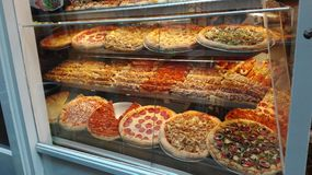 Showcase full of large, colorful and stuffed pizzas stock photo