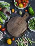 Food background. Assortment of fresh vegetables around the cutting board on a dark background. Top view, free space for text Stock Photos