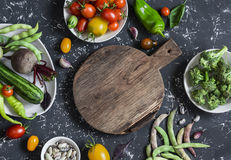 Food background. Assortment of fresh vegetables around the cutting board on a dark background. Top view. Free space for text Royalty Free Stock Images