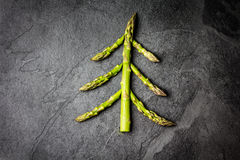 Food background. Christmas tree made from asparagus Healthy holiday concept. Christmas Food background. Christmas tree made from fresh asparagus on black stone Royalty Free Stock Photos