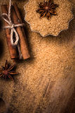 Food background with copy space. Brown sugar, anise star and cinnamon sticks on wooden background close up, still life. stock image