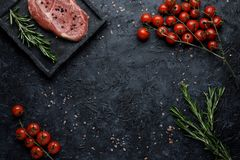 Food background with copy space. Raw rib eye steak with tomatoes and rosemary on black background top view. royalty free stock photos