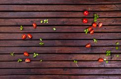 Spices, cherry tomatoes, basil and vegetable oil on dark wooden table, top view royalty free stock images
