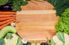 Food background with copy space for text. Fresh organic vegetables: carrots, salad, garlic, dill, cauliflower around wooden board. Food background with copy Stock Photography