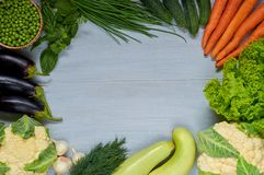 Food background with copy space for text. Fresh organic vegetables: carrots, zucchini, eggplants, garlic, peas, basil, dill, onion. Raw ingredients for salad Stock Photography