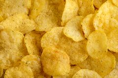 Food background of delicious chips. Corrugated golden chips potato texture royalty free stock photography