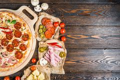 Food background design. Large authors meat pizza from four diff. Erent parts on a round cutting board on a dark wood. Ingredients royalty free stock images