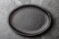 Food background. Empty cast iron black plate. Copy space Royalty Free Stock Image