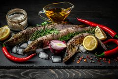 Food background for fish pike dishes cooking with various ingredients. Raw pikes with oil, herbs and spices on cutting board , top stock photography