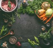 Food background frame with ingredients for tasty Ham Hock Soup : raw beef meat shin with bone, root vegetables, herbs and spices. On dark rustic kitchen table stock photography