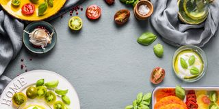 Food background with fresh colorful tomatoes, Mozzarella cheese with olives oil and basil leaves on kitchen table, top view. royalty free stock images