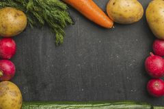 Fresh raw vegetables on a black background. Food background. Fresh farmer vegetables at dark table. Space for text Stock Images