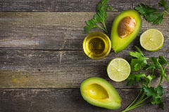 food background with fresh organic avocado, lime, parsley and olive oil royalty free stock photos
