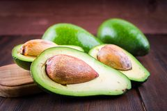 Food background with fresh organic avocado on old wooden table, Royalty Free Stock Images