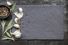 Food Background Garlic Sage and peppercorns on Slate Top View. Food background on slate, top view, with garlic cloves, sage leaves and peppercorns Royalty Free Stock Photo