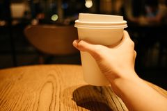 Food background hand of woman holding coffee glass in restaurant. With copy space. image for cafe, beverage, indoor, object, lifestyle concept royalty free stock photography