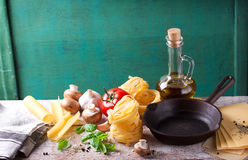 Food background or healthy concept with olive oil, fresh basil, pasta tagliatelle, mushrooms, tomatoes, pepper and cooking pan Royalty Free Stock Images