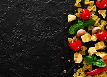 Farfalle pasta, red chili peppers, cherry tomato, basil, black pepper, garlic, parmesan cheese on dark background Royalty Free Stock Photo