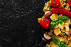 Farfalle pasta, red chili peppers, cherry tomato, basil, black pepper, garlic, parmesan cheese on dark background stock photography