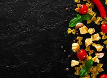 Farfalle pasta, red chili peppers, cherry tomato, basil, black pepper, garlic, parmesan cheese on dark background stock image