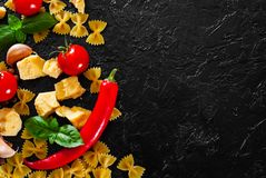 Farfalle pasta, red chili peppers, cherry tomato, basil, black pepper, garlic, parmesan cheese on dark background Royalty Free Stock Image