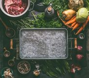 Food background. Ingredients for tasty Ham Hock Soup : raw beef meat shin with bone, root vegetables, herbs and spices around tray. On dark rustic kitchen table royalty free stock photo