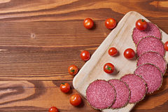 Food background of italian delicacy salami on wooden board Stock Photos