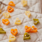 Food background. Italian tricolor pasta in the shape of hearts on the kitchen textiles. Selective focus. Close-up. Food background. Pasta hearts on the kitchen Royalty Free Stock Image