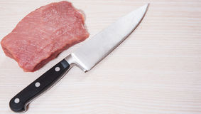 Food background of knife and raw meat at the wooden board. With copy space Royalty Free Stock Photography